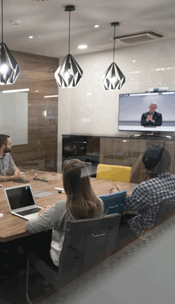 Group in a conference room watching a video