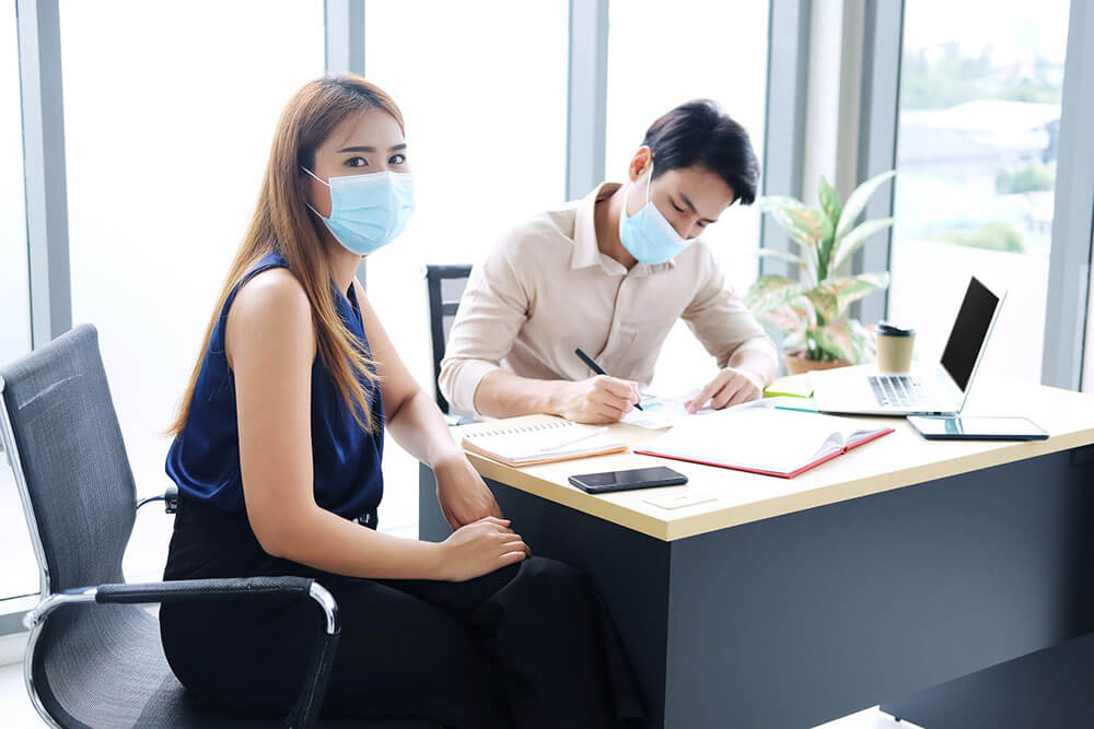 Two coworkers in masks