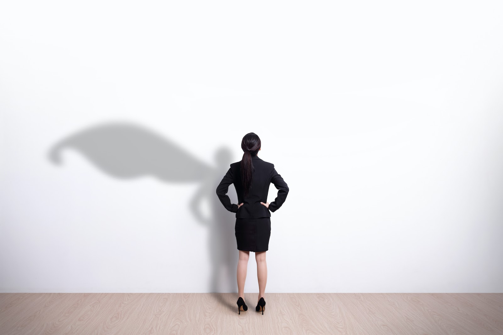 Woman looking at her shadow with a cape